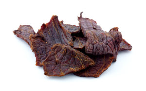 A side view of slow cured beef jerky against a white background.